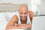 Smiling casual bald young man using laptop in bed