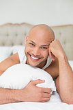 Smiling casual bald young man lying in bed