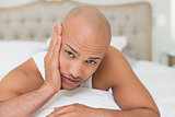 Bald man suffering from toothache in bed