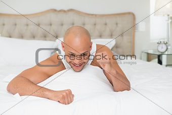 Close up of a man cheering in bed