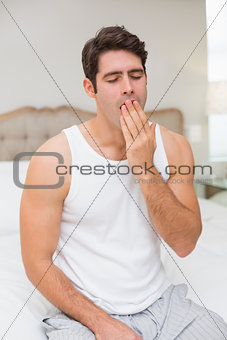 Young man yawning in bed at home