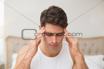 Close up of a man suffering from headache in bed