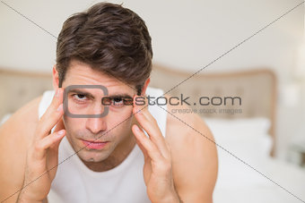 Close up of man suffering from headache in bed