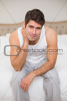 Portrait of man suffering from neck ache in bed