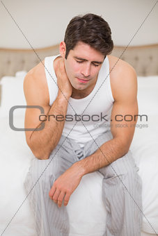 Young man suffering from neck ache in bed