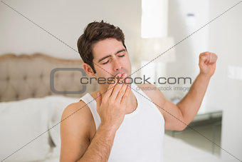 Young man waking up in bed and stretching arms