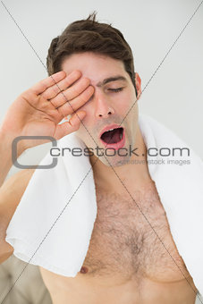 Shirtless man yawning as he rubs his eye