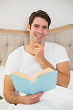Portrait of relaxed young man reading book in bed