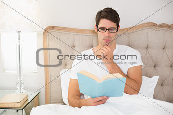 Relaxed young man reading book in bed