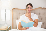 Portrait of relaxed man reading book in bed