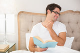 Smiling relaxed man reading book in bed
