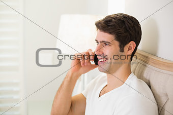 Casual smiling man using cellphone in bed
