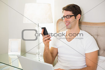 Casual smiling man text messaging in bed