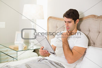 Casual man reading newspaper in bed