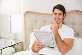 Smiling casual man reading newspaper in bed
