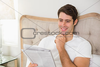 Casual smiling man reading newspaper in bed