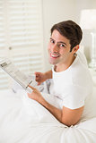 Portrait of smiling casual man reading newspaper in bed