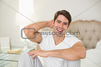 Portrait of cheerful young man sitting in bed