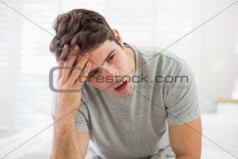 Sleepy young man yawning in bed