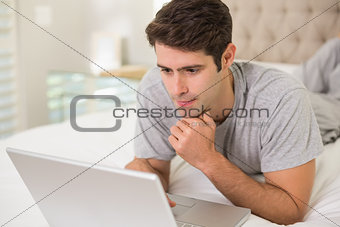 Casual young man using laptop in bed