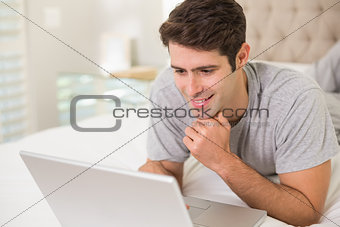 Casual smiling man using laptop in bed