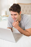 Casual smiling young man using laptop in bed