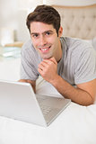 Portrait of a casual smiling young man using laptop in bed