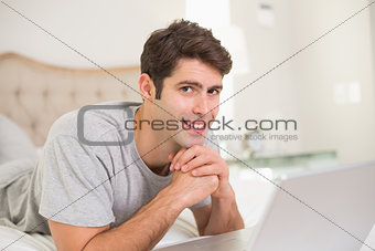 Portrait of casual smiling man using laptop in bed