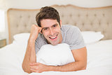 Close up portrait of smiling man resting in bed