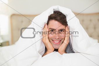 Close up portrait of a smiling man resting in bed