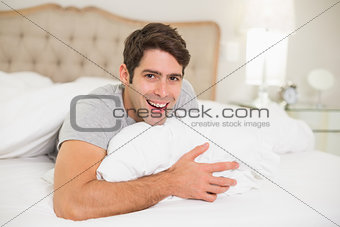 Close up portrait of a cheerful man resting in bed