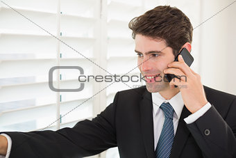 Smiling businessman peeking through blinds while on call