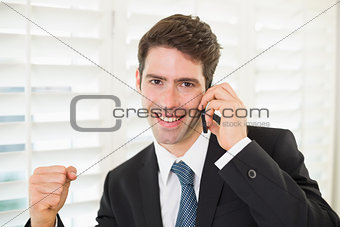 Portrait of smiling businessman using mobile phone while clenching fist