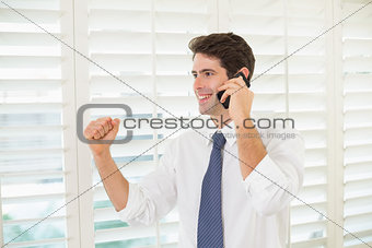 Smiling businessman using mobile phone while clenching fist
