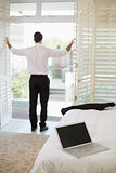 Businessman looking through window at a hotel bedroom