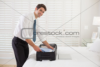 Smiling businessman unpacking luggage at a hotel bedroom