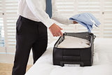 Mid section of businessman unpacking luggage at hotel