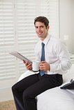 Businessman with coffee cup and newspaper at hotel room
