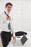 Smiling businessman wearing tie while using laptop at hotel room