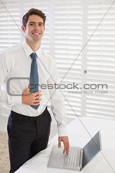 Smiling businessman using laptop at hotel room