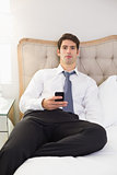 Serious well dressed man with cellphone sitting in bed