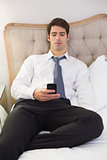 Serious well dressed man text messaging in bed