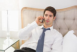 Serious well dressed man using mobile phone in bed