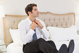 Elegant young businessman adjusting tie in bed