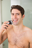 Smiling handsome shirtless man shaving with electric razor