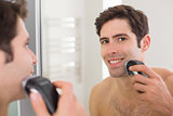 Reflection of shirtless man shaving with electric razor