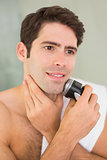Handsome shirtless man shaving with electric razor