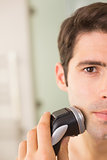Handsome man shaving with electric razor
