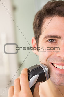 Close up of smiling man shaving with electric razor