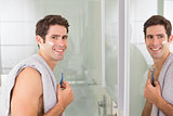 Smiling handsome man with reflection shaving in bathroom